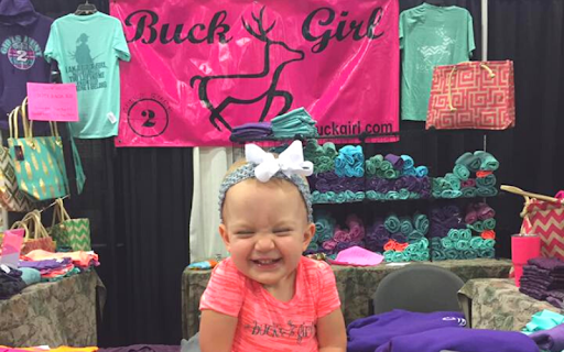 Cute Baby Sitting in front of Buck Girl's Apparel Booth