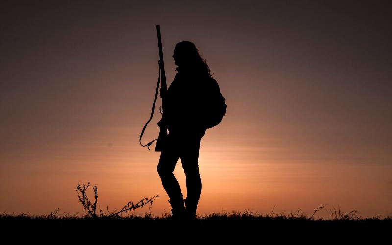 Woman Hunter Silhouette Against Sunrise